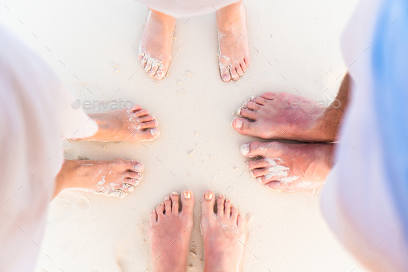 Close-up of the feet of family on the white sandy beach - Stock Photo - Images