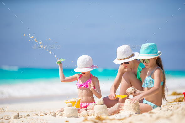 Mother and little daughters making sand castle at tropical beach - Stock Photo - Images