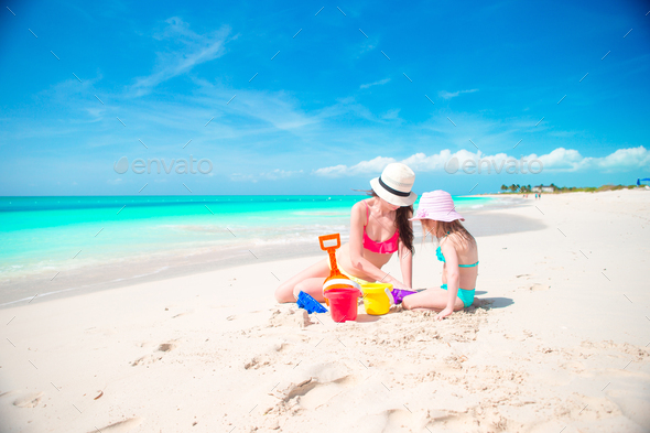 Mom and little cute baby making sandcastle at tropical beach - Stock Photo - Images