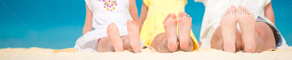 Closeup of the feet of family on the white sandy beach - Stock Photo - Images