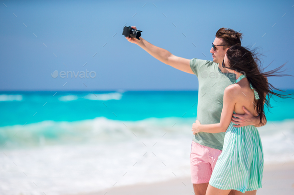 Happy couple taking a photo on a beach on holidays - Stock Photo - Images