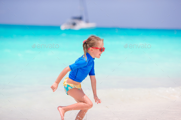 Adorable little girl having fun in shallow water - Stock Photo - Images