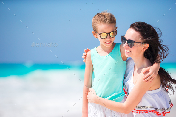Portrait of little adorable girl and young mother at tropical beach - Stock Photo - Images