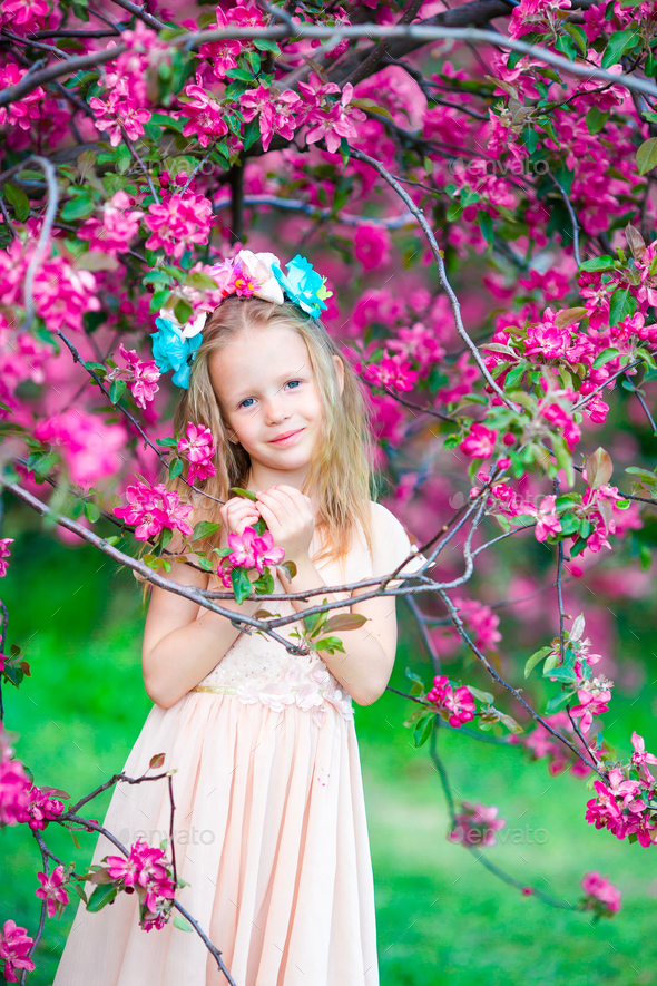 Cute girl in blooming apple tree garden enjoy the warm day - Stock Photo - Images