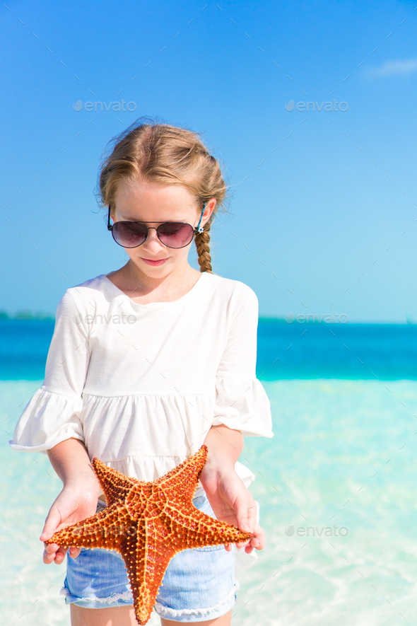 Adorable little girl with starfish on white empty beach - Stock Photo - Images