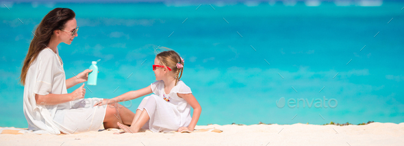 Young mother applying sun cream to daughter nose on bach vacation in hot day - Stock Photo - Images