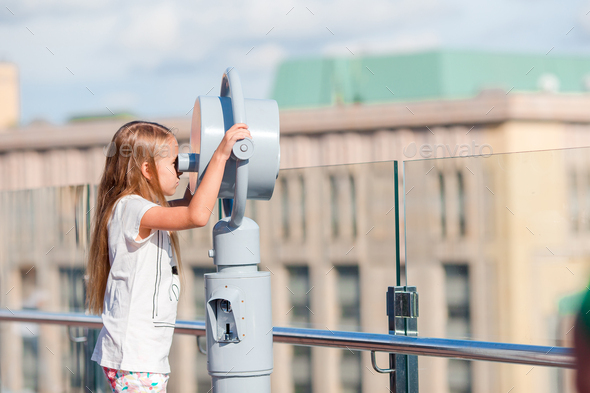 Little girl looking at coin operated binocular on terrace with beautiful view - Stock Photo - Images