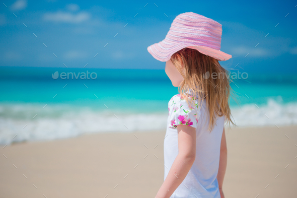 Adorable little girl walking along white sand Caribbean beach - Stock Photo - Images