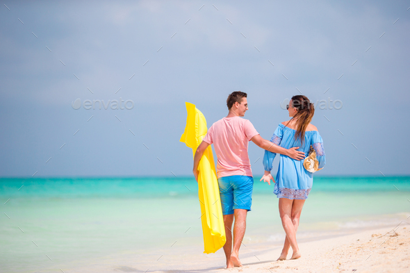 Rear view of happy couple in honeymoon on the beach - Stock Photo - Images