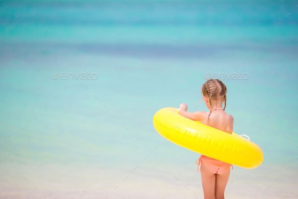Adorable girl with inflatable rubber circle going to swim - Stock Photo - Images