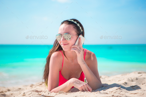 Young woman with cell phone lying on white beach - Stock Photo - Images