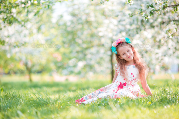 Adorable little girl in blooming cherry tree garden on spring day - Stock Photo - Images