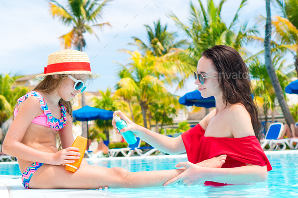 Young mother applying sun cream to daughter nose in pool - Stock Photo - Images