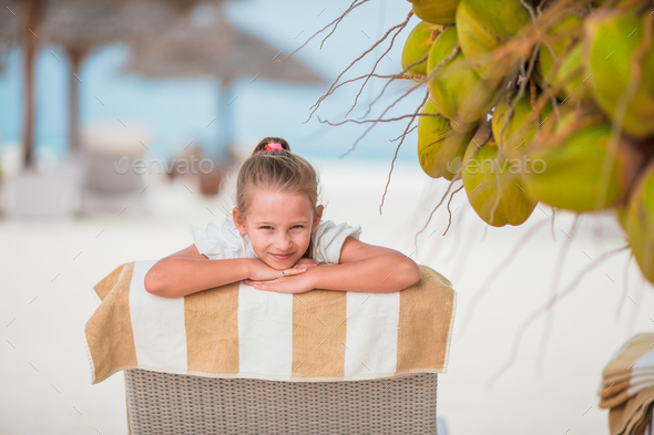 Adorable girl on lounger at tropical exotic beach under big coconuts - Stock Photo - Images