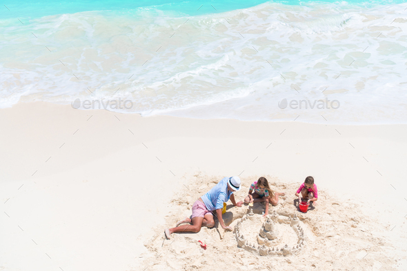 View from above to father and little daughters making sand castle at tropical beach - Stock Photo - Images