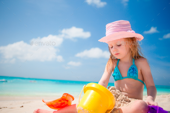 Little girl playing with beach toys during tropical vacation - Stock Photo - Images