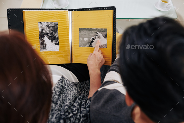 Mother showing son wedding photos - Stock Photo - Images