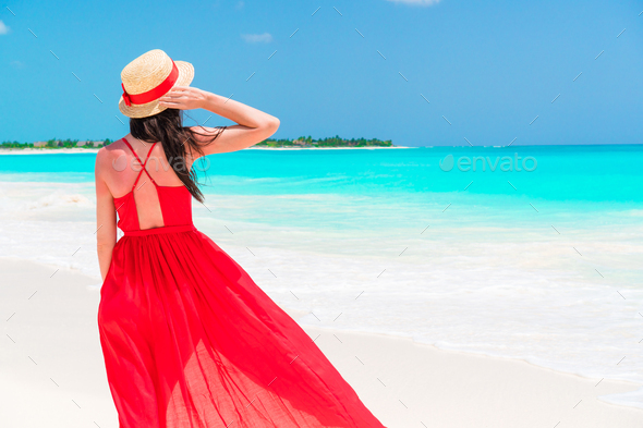 Beautiful woman on tropical seashore. Young girl in beautiful red dress background the sea - Stock Photo - Images
