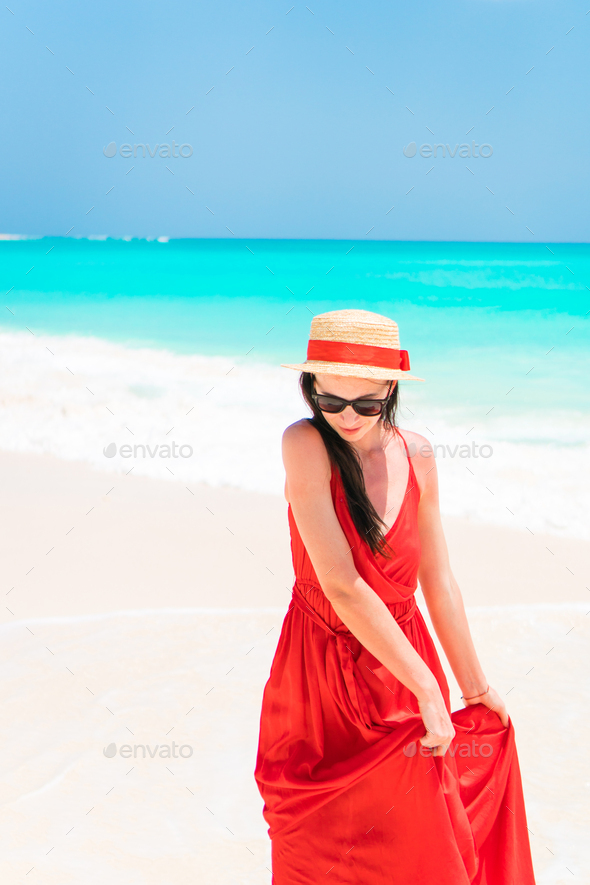 Beautiful woman on tropical seashore. Young girl in beautiful dress background the sea - Stock Photo - Images