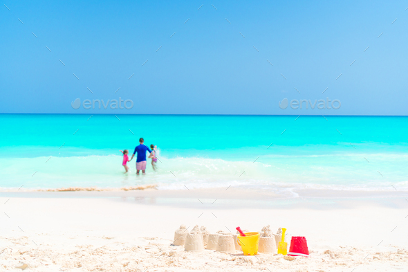 Sandcastle at white beach with plastic kids toys and family in the sea background - Stock Photo - Images