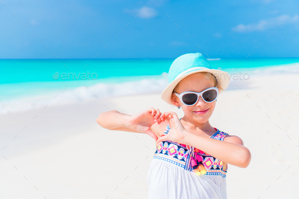 Little girl in hat walking at beach during caribbean vacation - Stock Photo - Images