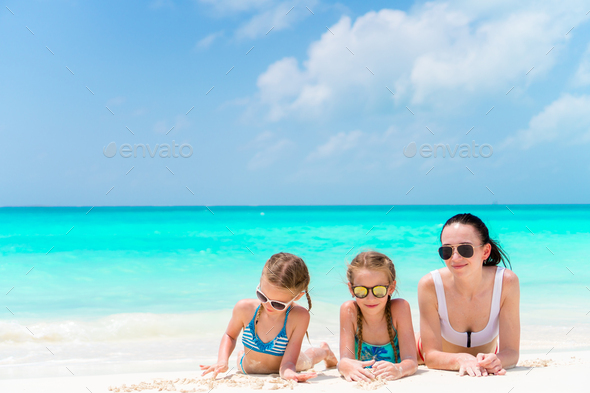 Portrait of young beautiful mother and her adorable little daughters at tropical beach - Stock Photo - Images
