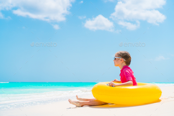Adorable little girl with inflatable rubber circle have fun on the beach - Stock Photo - Images