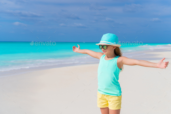 Cute little girl in hat walking at beach during caribbean vacation - Stock Photo - Images