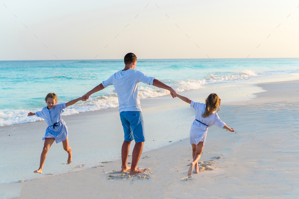 Family walking on white beach on caribbean island in the evening - Stock Photo - Images