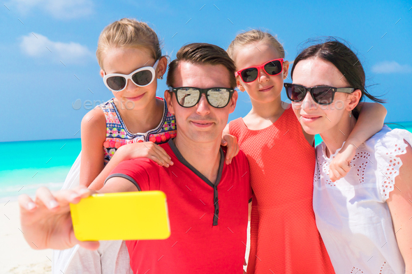 Young beautiful family taking selfie portrait on the beach - Stock Photo - Images
