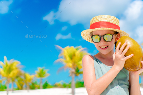 Little happy girl with big coconut on the beach - Stock Photo - Images
