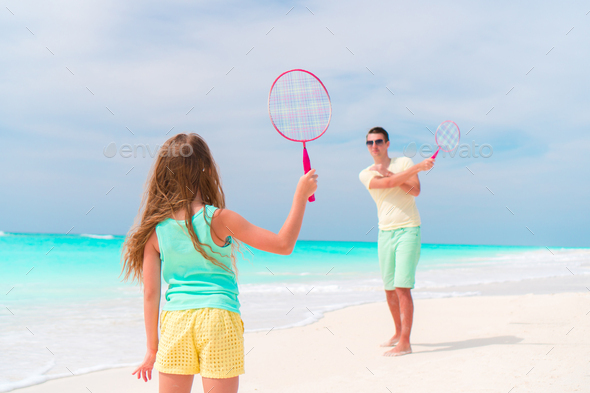 Little girl playing beach tennis on vacation with dad - Stock Photo - Images