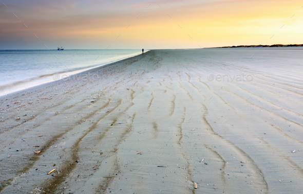 lone silhouette on North sea sand beach at dawn - Stock Photo - Images