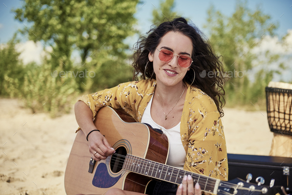 Beautiful woman playing the guitar on the beach - Stock Photo - Images
