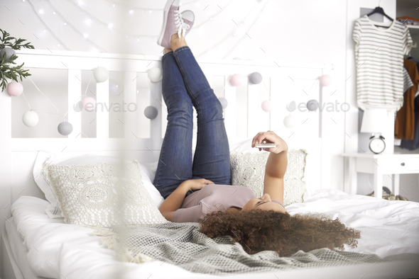 Teenage girl lying on the bed and making a selfie - Stock Photo - Images
