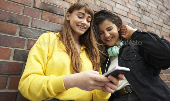 Low angle view of girls with mobile phone - Stock Photo - Images