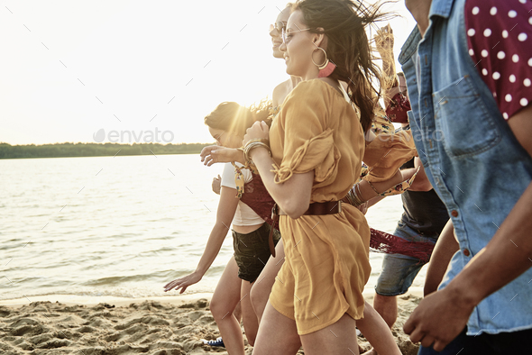 Group of young people running on the beach - Stock Photo - Images