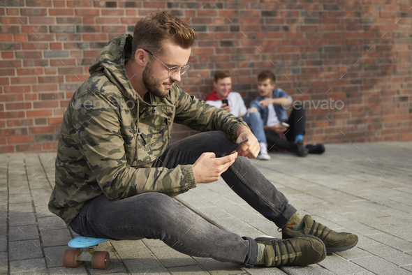 Handsome man using mobile phone and sitting on skateboard - Stock Photo - Images