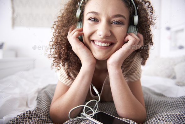 Portrait of smiling teenage girl listening to music in bedroom - Stock Photo - Images