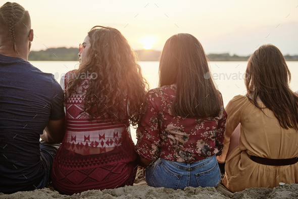 Rear view of young people chilling outside - Stock Photo - Images
