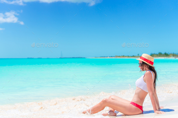 Young woman on a tropical beach with hat - Stock Photo - Images