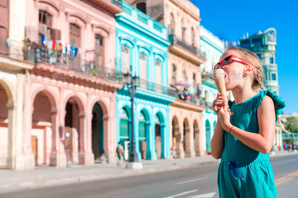 Adorable little girl eating ice-cream in popular area in Old Havana, Cuba. Portrait of cutiest kid - Stock Photo - Images