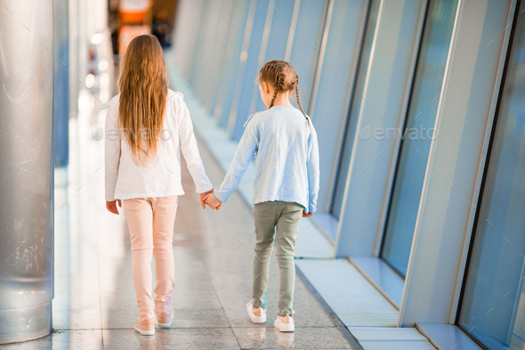Little adorable girls in airport near big window - Stock Photo - Images