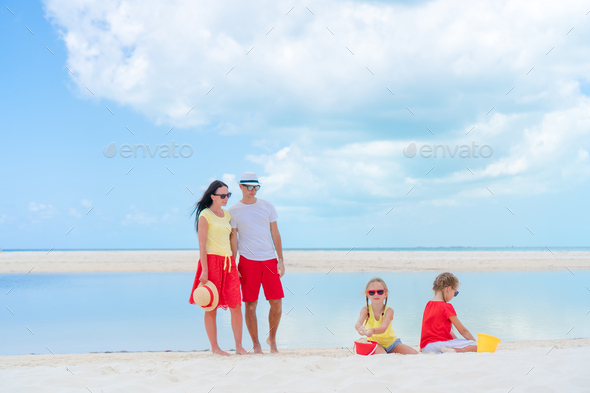 Family of four on a tropical beach - Stock Photo - Images