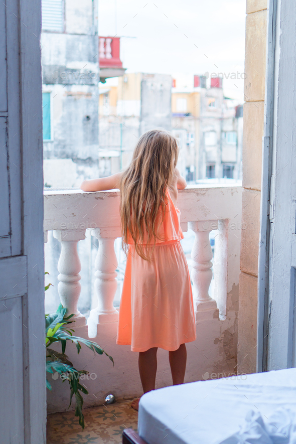 Little girl on old balcony in apartment looking on the street in Old Havana, Cuba - Stock Photo - Images