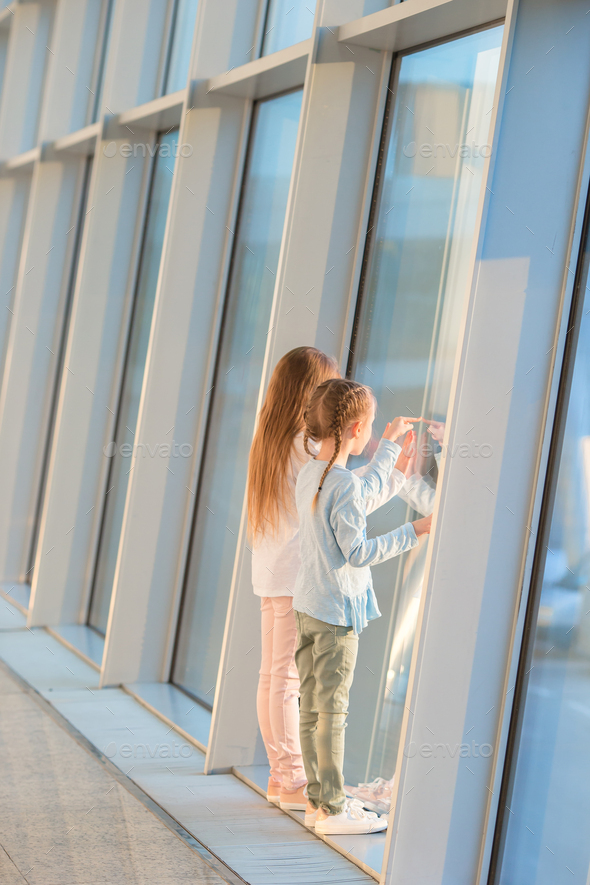 Little kids together in airport waiting for boarding near big window - Stock Photo - Images
