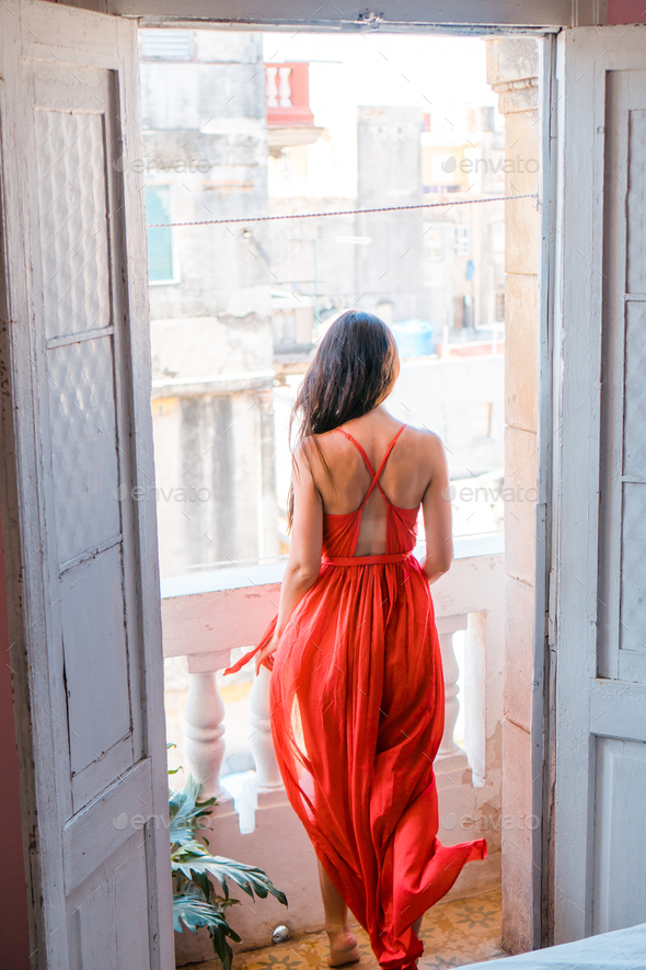 Young attractive woman in red dress on old balcony in apartment in Havana - Stock Photo - Images