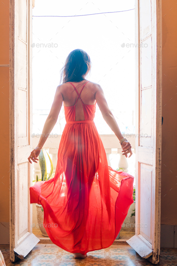 Young beautiful woman in red dress on old balcony in apartment in Old Havana, Cuba - Stock Photo - Images