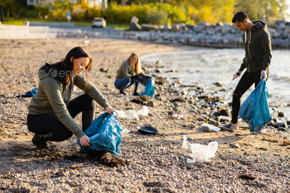 Young woman picking up garbage in bag at beach - Stock Photo - Images