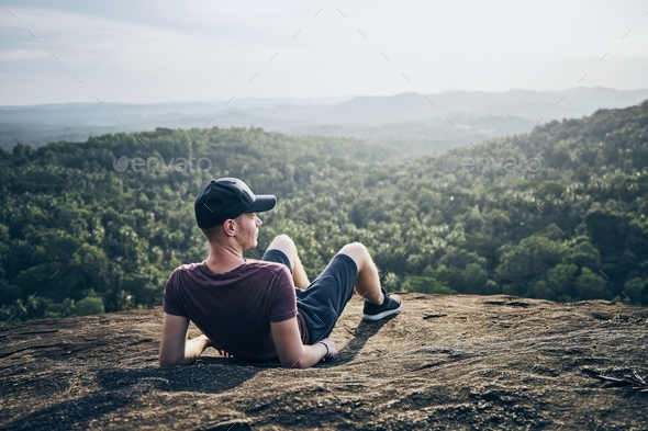 Man resting on rock over jungle - Stock Photo - Images